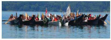 "Canoe Families rafted up together to create a ""Flotilla"" of canoes while they awaited to come ashore."